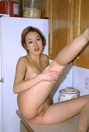 Asian amateur Hazel revealing pierced nipple and bald cunt in kitchen
