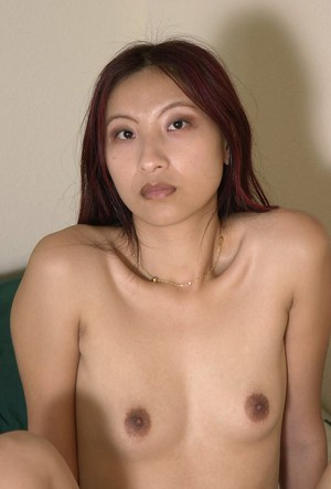 Hot Asian chick Mai baring small tits and hairy cunt while undressing