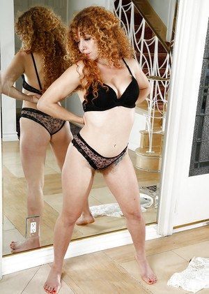 Mature redhead Leona stripping off sexy lingerie to expose hairy vagina