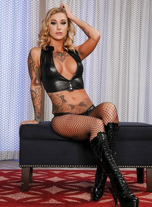 Tattooed model Kleio Valentien strutting in mesh stockings and knee high boots