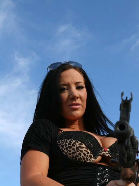 Gigantic titted pornstar Jayden Jaymes poses unclothed with a gun alfresco