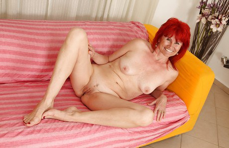 Redheaded granny Patricie spreading muffin and playing with jugs