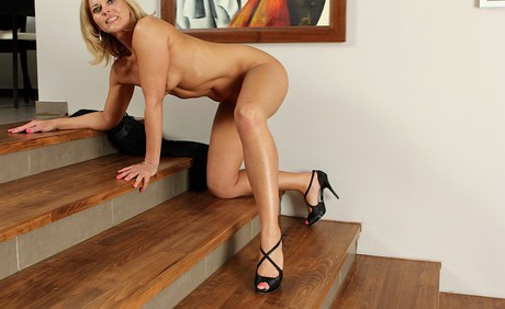 Blond consort Carrie teases her milf moggy while posing on stairs