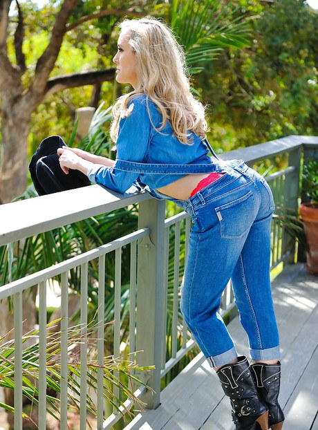 Voluptuous Milf over 40 Brandi Adore posing in cowgirl boots with gun outside