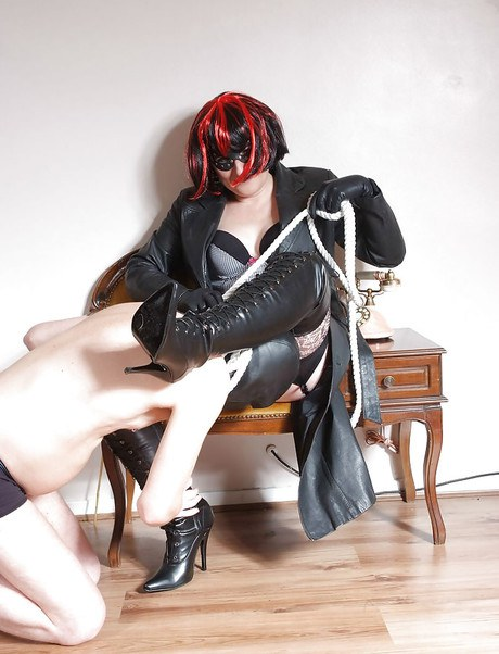 Lumpy domme in femur high leather shoes leads man servant by cord