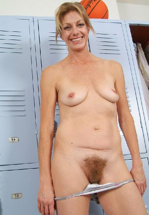 Cute mom stripping in a locker room and reveals her hairy bush from panties
