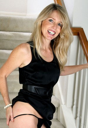 Mature blonde revealing small tits and fondling her pussy on the stairs