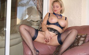 Mature blonde with massive boobs spreading her legs to expose her shaved cunt