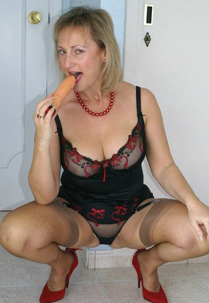 Fat mommy in stockings and black lingerie sucking a dildo and masturbating