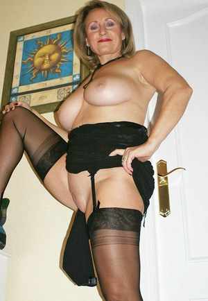 Big titted mature woman in black lingerie shoving panties in her shaved pussy