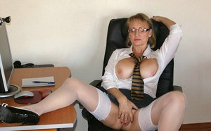 Busty mature secretary in stockings and glasses masturbating in the office