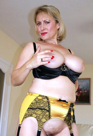 Tempting blond mom in shiny stockings and gold garters exposing her bush