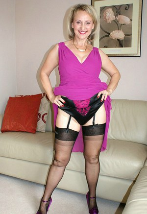 Voluptuous mature lady strips to her sleek lingerie and plays with her snatch