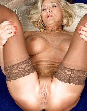 Mature blond spreading her stockinged legs to insert a toy into her wet cunt