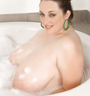 Chubby girl Alice Webb goes horny while massaging her tits in a foamy bathtub