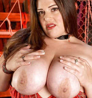 Plump vixen Angel Sin strips from red corset and skirt to play with fetish toys