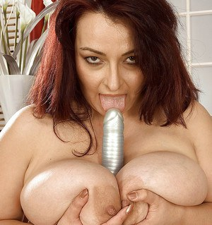 Fat brunette goes naughty and inserts a silver dildo between her legs and juggs