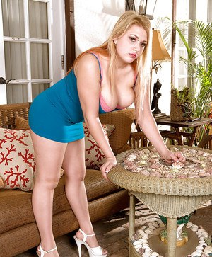 Busty blond Shyla Shy posing in miniskirt and heels with her boobies exposed