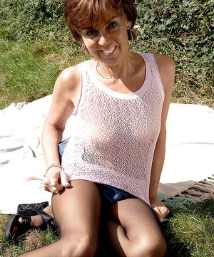 Raunchy mature woman in black torn pantyhose flashing tits on the picnic