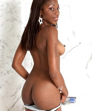 Black babe gets in the bath and plays with her shaved twat.