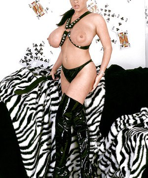 Big titted fetish model Linsey Dawn McKenzie posing in latex boots and belts