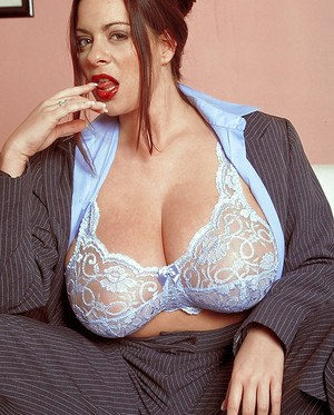 Fat MILF with big tits Linsey Dawn McKenzie posing in a suit.