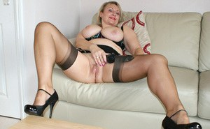 Passionate big breasted mature vixen relaxes on the sofa in her lingerie and pokes her seasoned snatch with her sex toy.