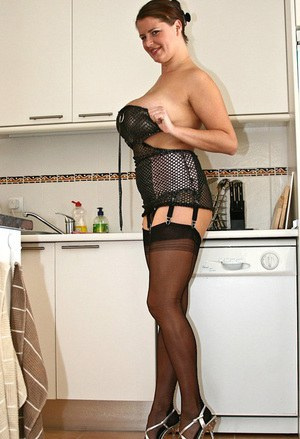 Busty fatty shows her large assets in the kitchen wearing fine black lingerie and nylon stockings.