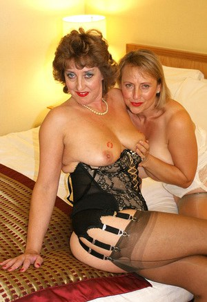 Two horny mature ladies dress up in sexy lingerie and play erotic lesbian games on the bed.