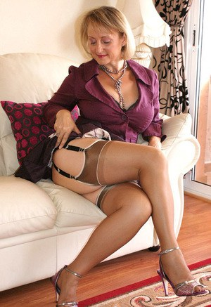 Classy blonde mature vixen takes off her sexy lingerie and plays with her massive big tits.