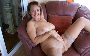 Alluring and smiling blonde fatty shows her shaved mature snatch in sexy stockings.