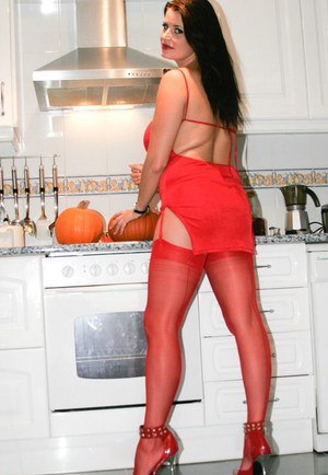 Seductive mature fatty shows her legs and sexy big breasts wearing classy red lingerie and stockings.