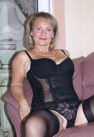 Busty blonde mature fatty teases our imagination by posing in classy black corset and nylon stockings.