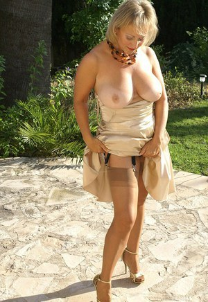 Alluring blonde mature fatty exposes her fantastic big breasts outdoors as she strips her sexy dress and stockings.