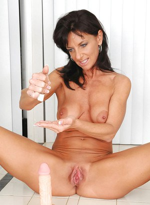 Fervent brunette MILF Sarah Bricks exposing shapely tits and toying shaved box