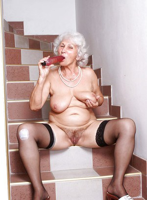 Fat granny in black hold up stockings squeezing a sex toy between her puffy tits