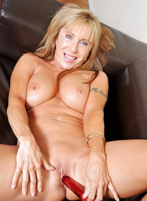 Busty mature sliding a long dildo deep inside her shaved pussy