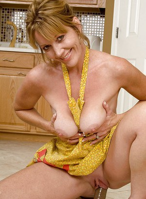 Chubby mature Samantha Stone has her big tits barely covered by apron