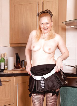 Chubby mature in maids uniform stripping to stockings in the kitchen