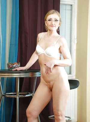 Seductive mature honey with glasses strips and shows her shaved wet cunt.