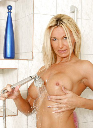 Blonde mature lady with big tits stripping in her bath.