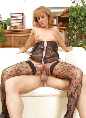 Lusty mature vixen in black body stockings shows off her tiny tits.