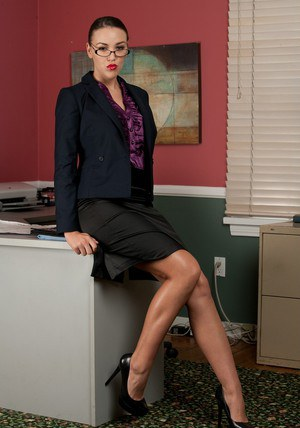 Busty office babe Emily Parker showing off curves and sexy tattoos
