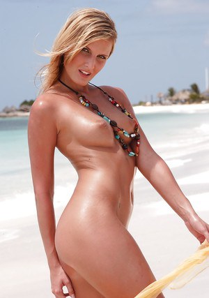 MILF pornstar flaunting nude and caressing small tits on the beach