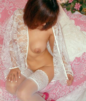 Tempting mom in white lacy lingerie and stockings strips in her bed