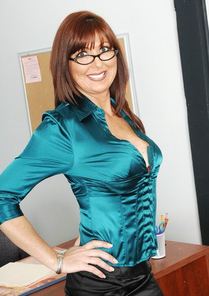 Mature teacher in glasses Desi Foxx strips to stockings in the class