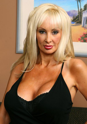 Big titted mature blonde Britanny O'Neil strips to black corset
