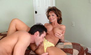 Striking mom with gorgeous breasts fucks younger guy and scores facial