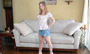 Puffy babe Sunny Lane stripping her skirt and exhibiting comely boobs
