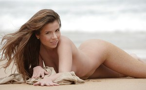 Pornstar babe exposing curvy butt and adorable boobies on the beach